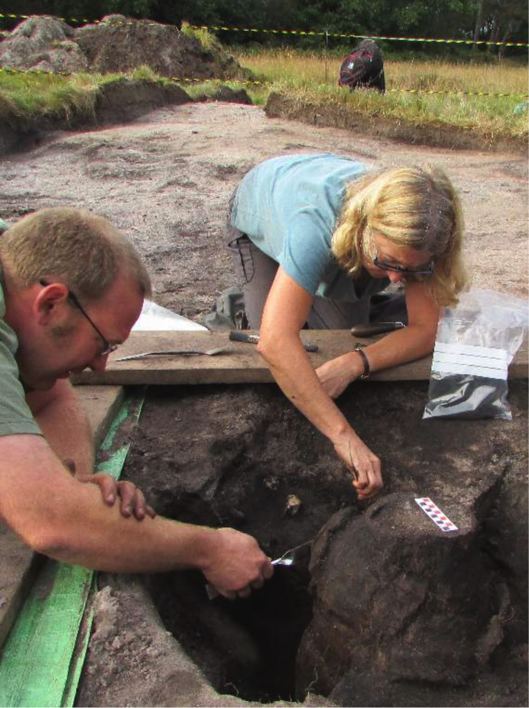 Dig director George Anelay (left) and volunteer Jane King uncover the burial urn